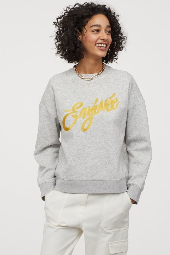 Smiling woman looking to the right wearing a grey sweater with gold text