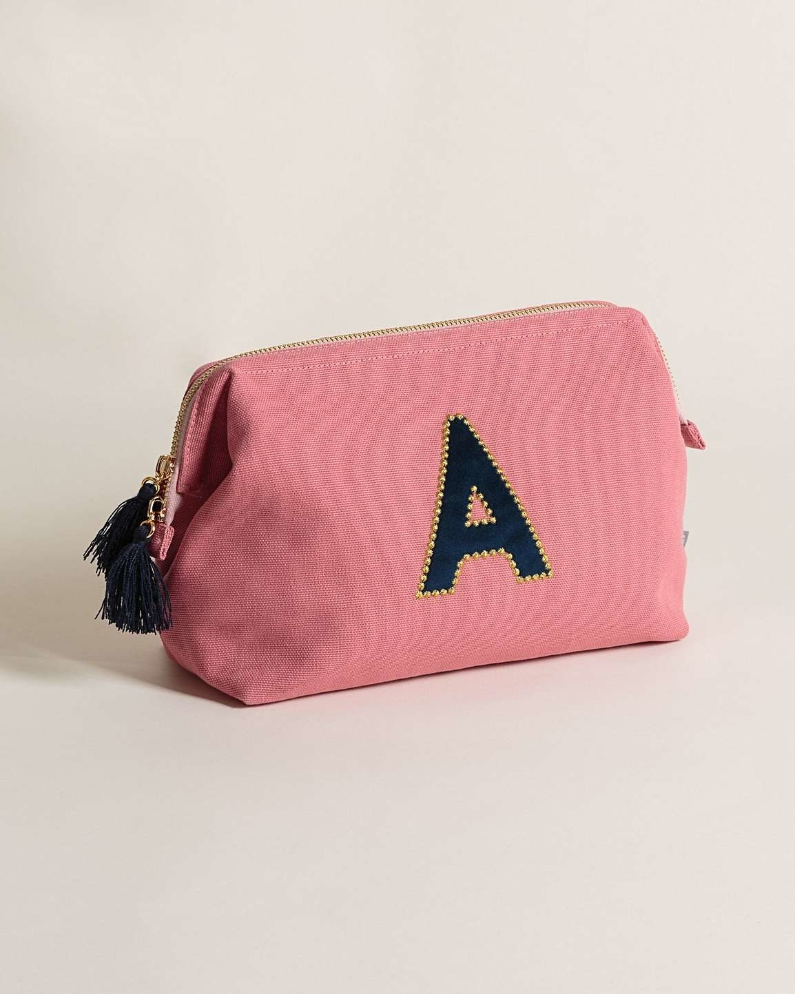 "Pink velvet wash bag with a black letter ""A"" on it and black fringing on the zip"