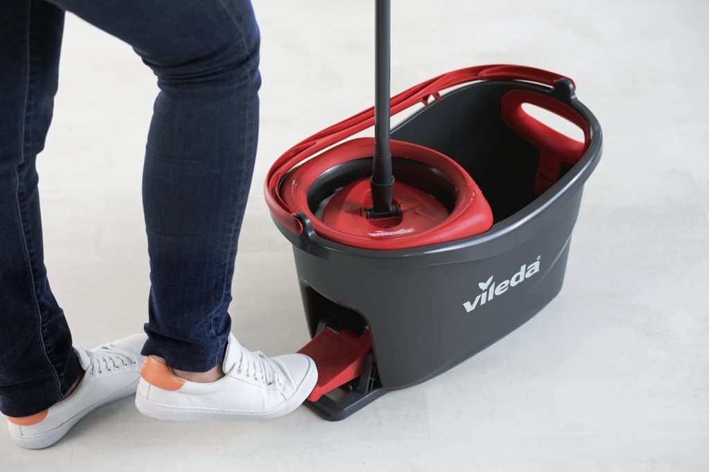 Foot pushing pedal on the back of a mop bucket