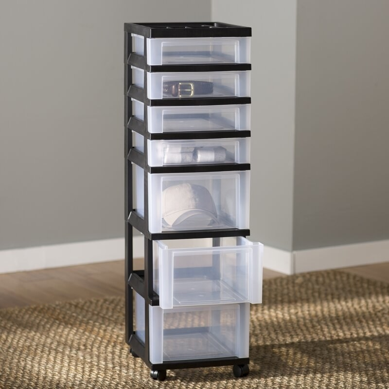 A clear plastic seven drawer chest with a black plastic frame on four caster wheels atop a brown rug