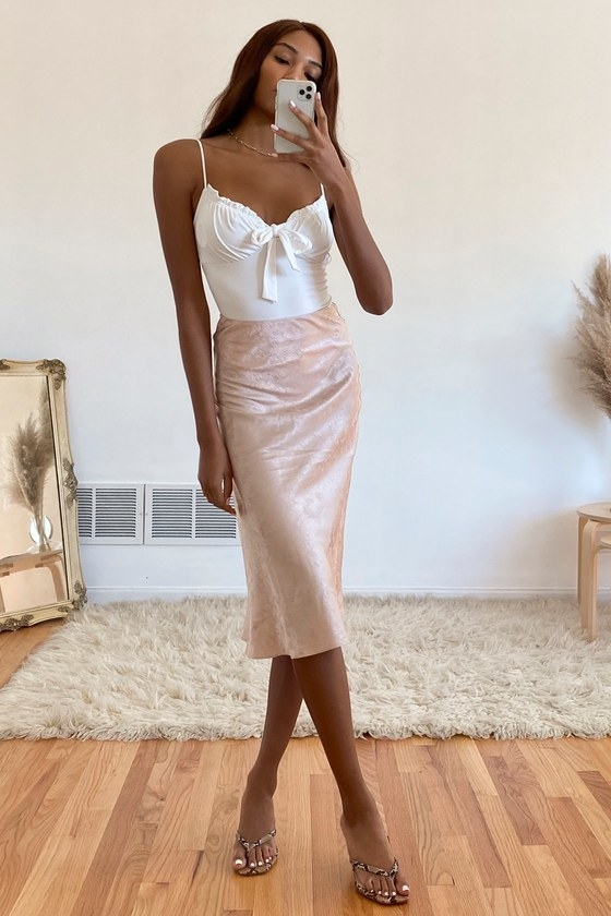 Model wearing blush pink satin midi slip skirt with a texted fabric, high-waist, and a-line silhouette