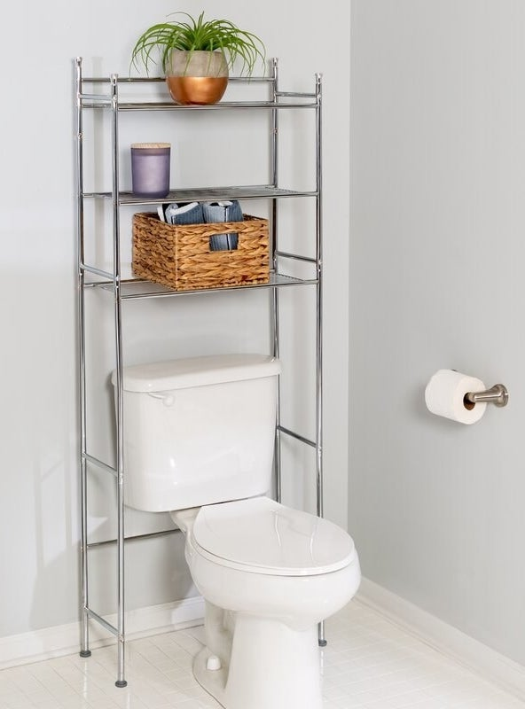 A chrome, metal, three-shelf organizer positioned over a white toilet bowl in a bathroom holding a plant, a candle and a wicker basket upon its shelves