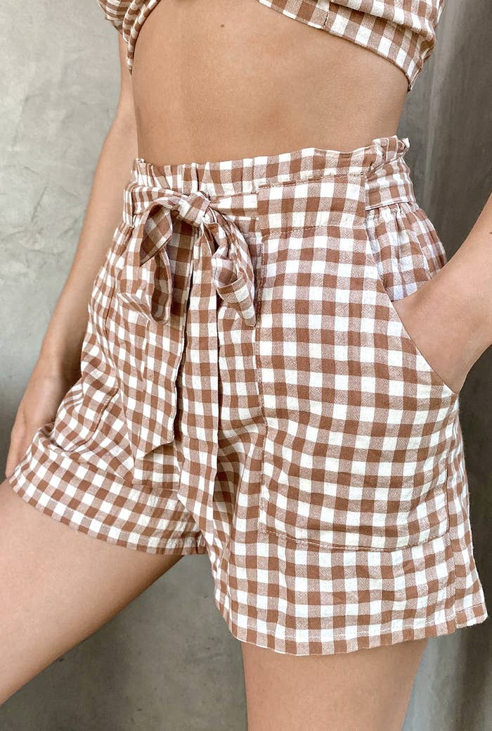 A close-up of a model wearing a pair of shorts with a brown and white checker pattern and a tie-waist front