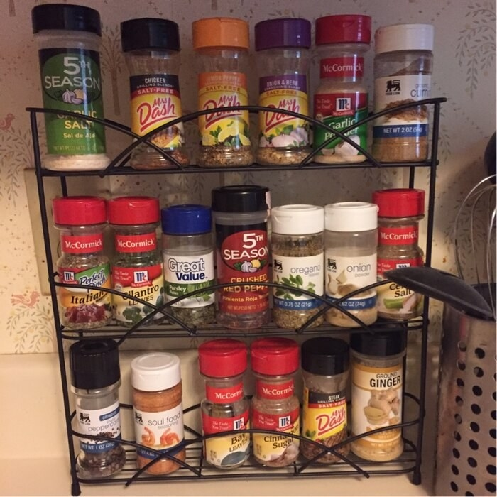 A black metal spice rack filled with various colorful spice jars sitting atop a kitchen counter