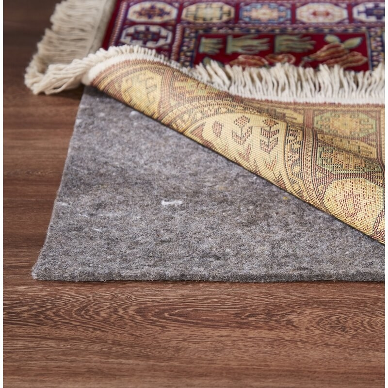 A rug with a corner lifted up to reveal the gray rug pad underneath