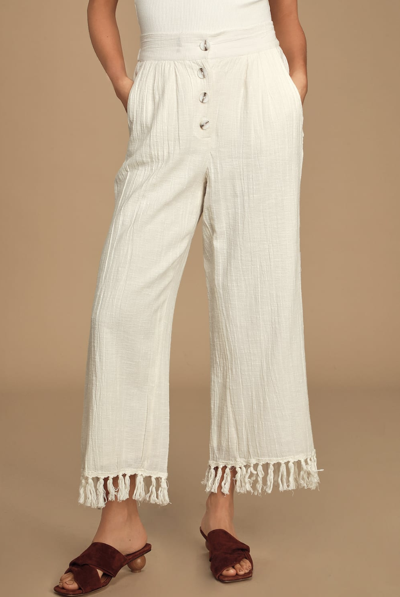 A waist-to-floor shot of the model wearing a pair of loose-looking white pants with a wide leg and tassels that hit their ankle