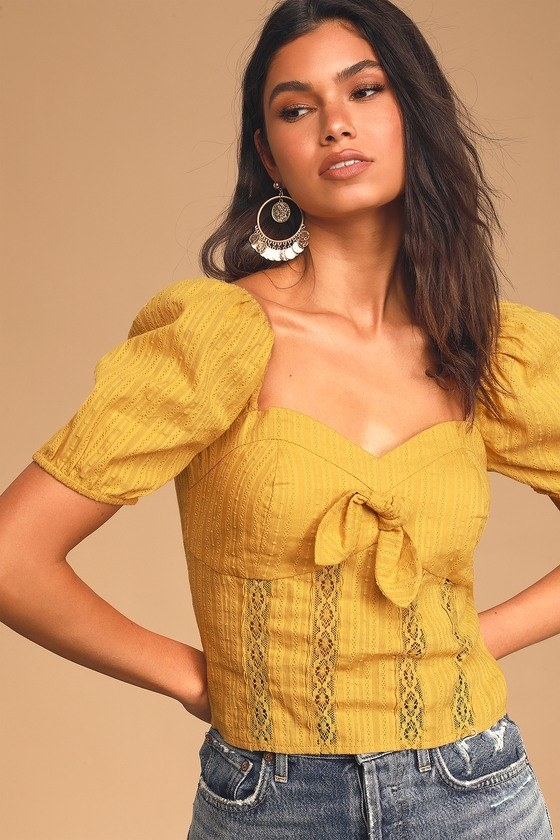 Model wearing mustard top with puff sleeve, sweetheart neckline, front tie, and strips of lace and embroidery down the front