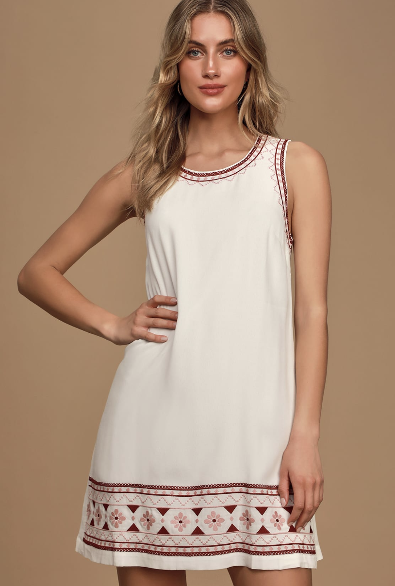 A model wearing a white, sleeveless dress that hits the upper thigh. The dress has thick straps and a brown and pink embroidery detail at the bottom and on the straps and neckline