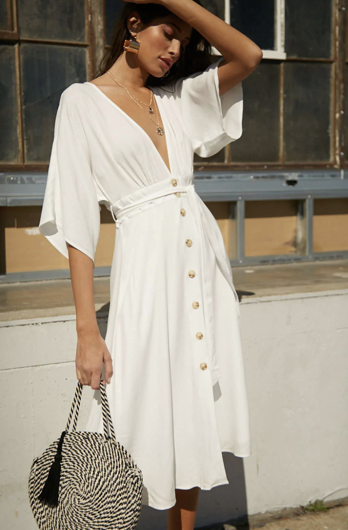 a person wearing a cream colored maxi dress with fluttery sleeves and buttons all down the middle