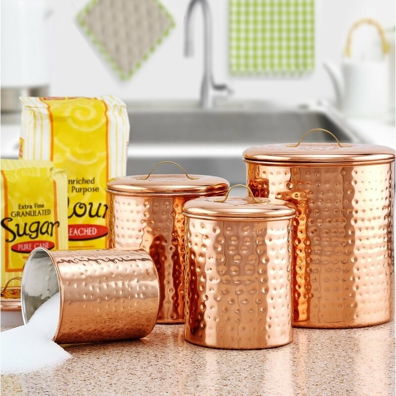 A set of four hammered copper canisters, the smallest of which is filled with sugar and tipped over spilling some out on a kitchen countertop
