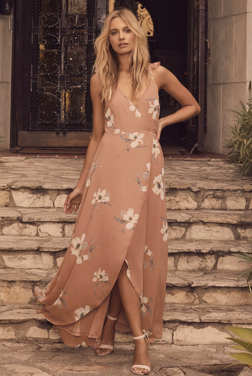 A full-body shot of the model wearing a light pink dress with white flowers designed on it. The dress is fitted at the waist but loose and flowy at the bottom