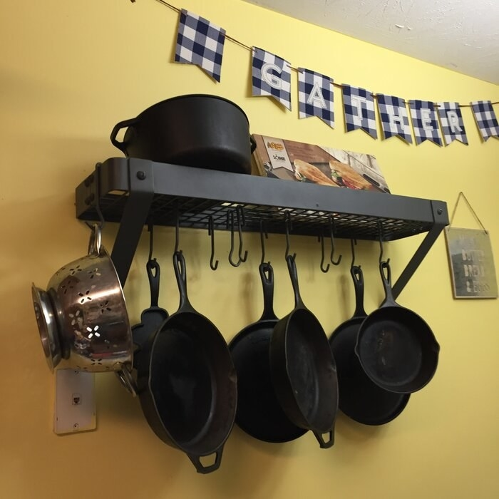 A graphite finish pot rack mounted on a yellow wall holding six heavy pans, a colander, and a pot