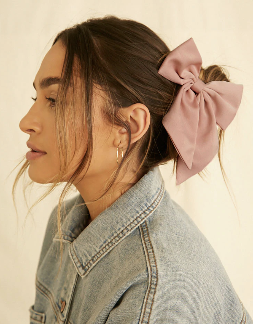 A person wearing their hair tucked into a bun with a silky scrunchie that has a hair bow already attached to it