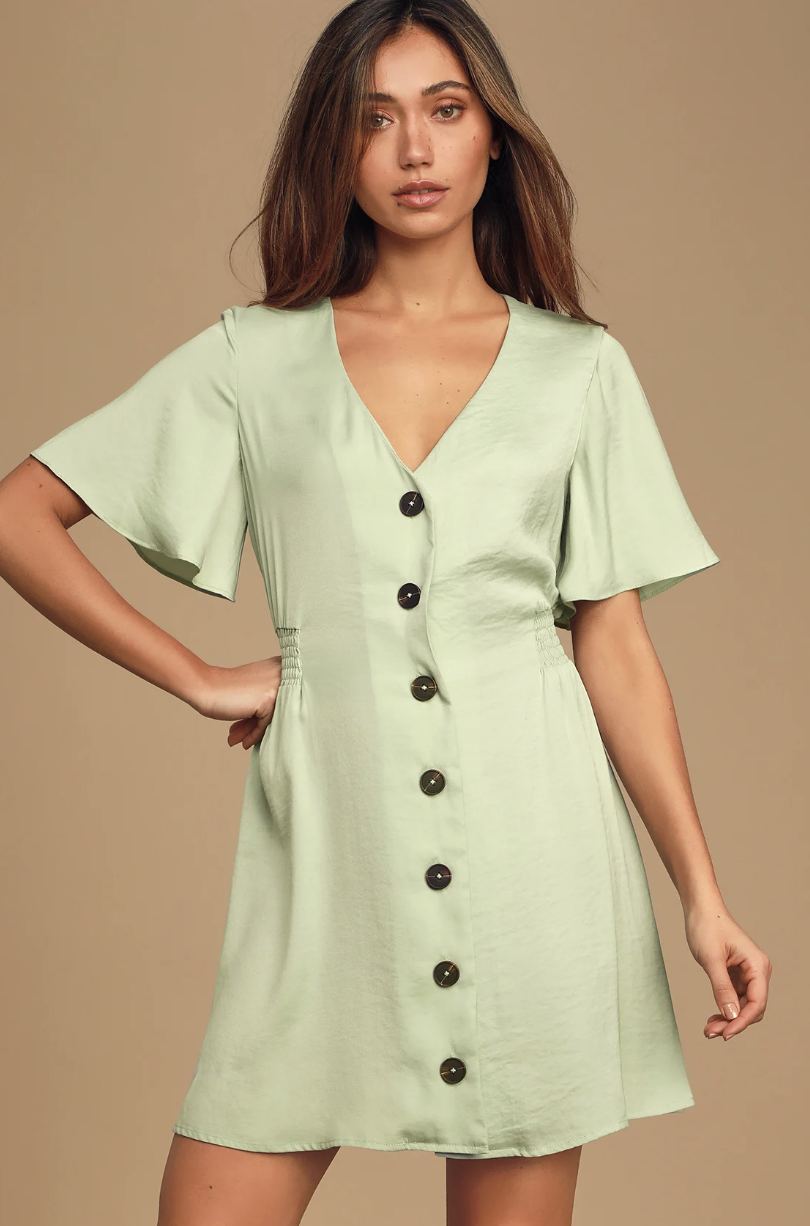 A model wearing a light, mint green colored dress that hits the model's upper thigh. The dress has loose short sleeves, a V-neck,  and large buttons running down the length of it
