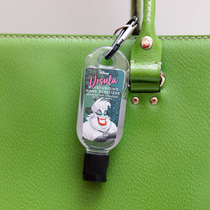 A small hand sanitizer tube with a picture of Ursula hanging off a purse