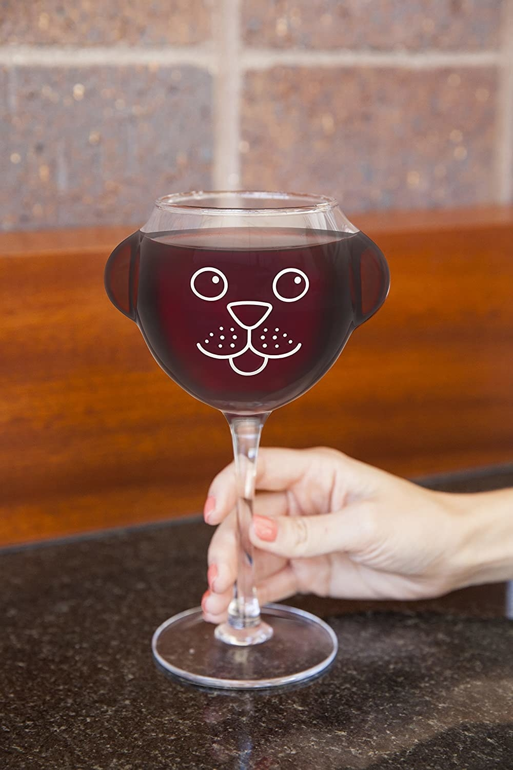 A long-stemmed transparent wineglass with a puppy face etched onto it and two glass puppy ears coming out the sides
