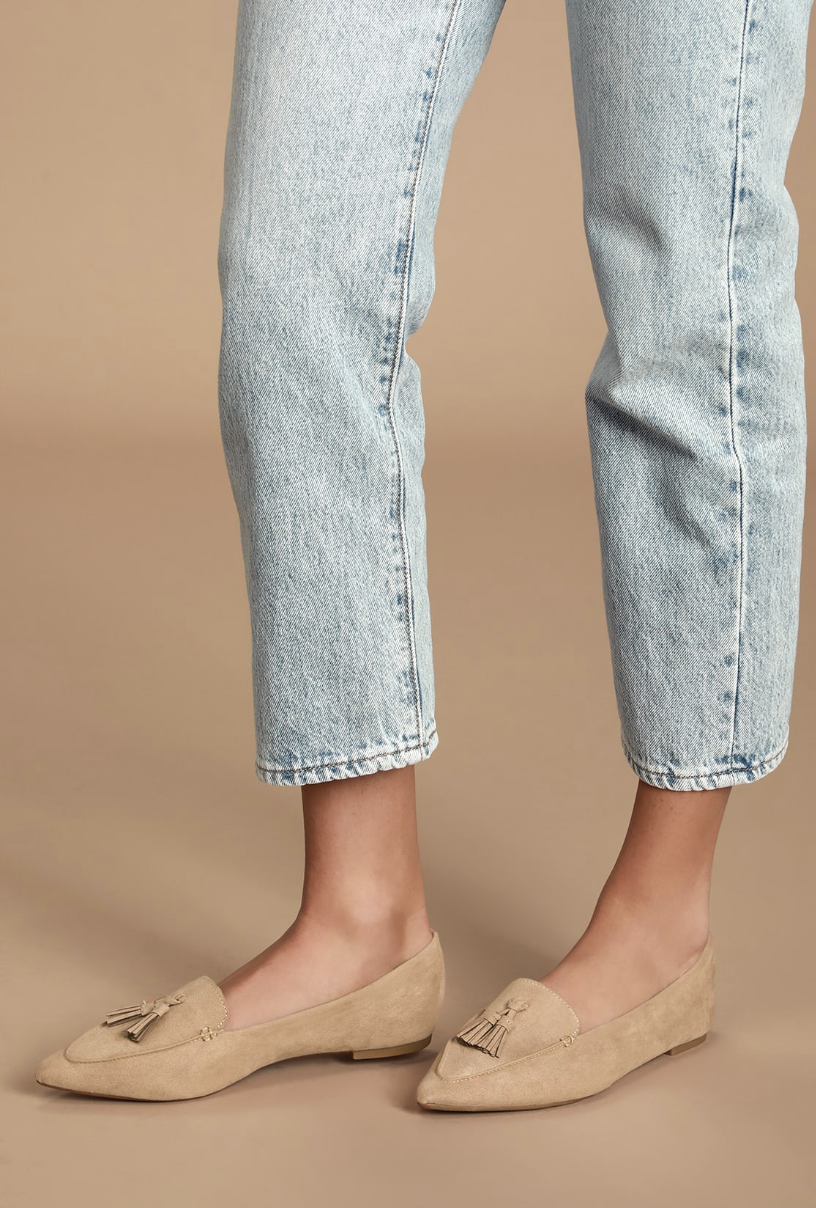 A shot showing the model wearing the tan loafers with a pointed toe and tassel detail on top