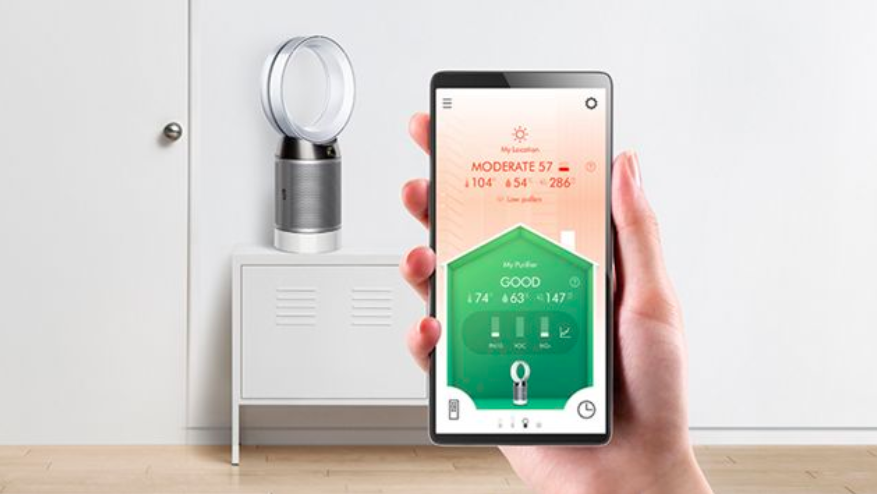 A picture of the Pure Cool DP04 purifying fan sitting on a table against a white wall with a hand holding up a phone in front of it displaying the notification of air quality provided by the fan.