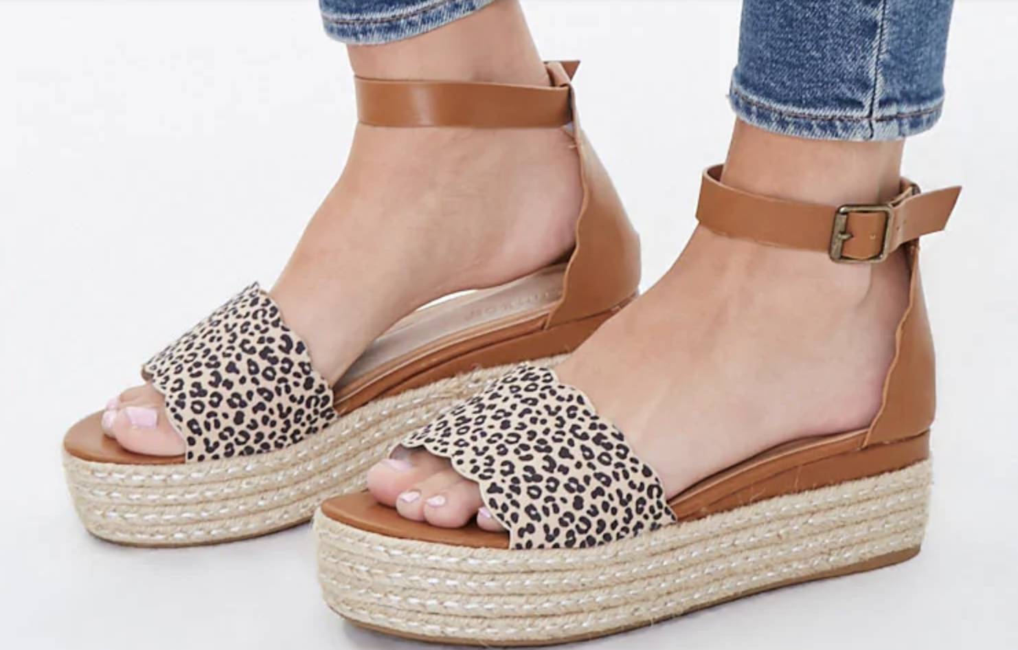 a pair of espadrilles with a straw-like platform, cognac colored straps around the ankle, and a leopard design across the toes with a scalloped cut