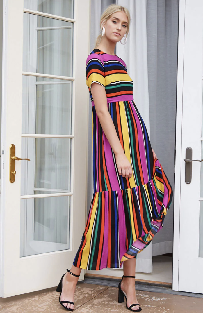 a person in black block heels standing in a doorway wearing a  t-shirt maxi dress with vertical colored stripes. The colors are orange, magenta, black, blue, white and green