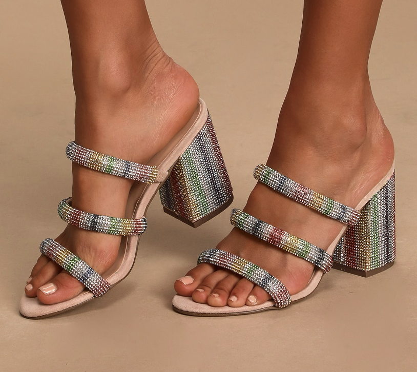 A close-up of a model wearing backless heels covered in small rainbow rhinestones and three straps across the width of the model's foot also covered in rainbow rhinestones