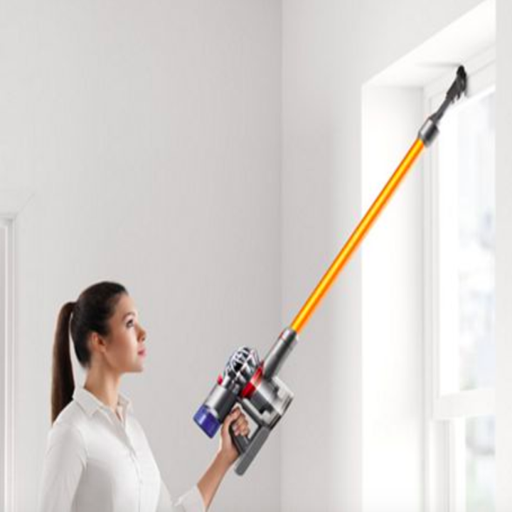 An image of a person using the V8 Absolute vacuum cleaner to clean the top part of a window.