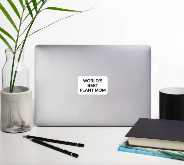 "An open laptop with the top facing the camera and a sticker in the center that reads ""World's Best Plant Mom"""
