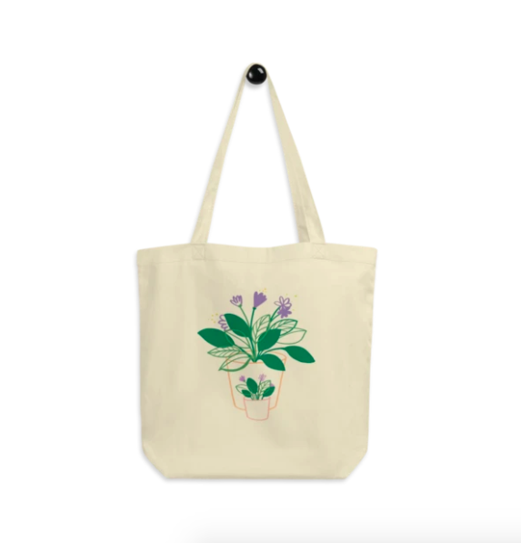 A cream tote bag with the illustration of two leafy plants with purple flowers on the front, one big, one small