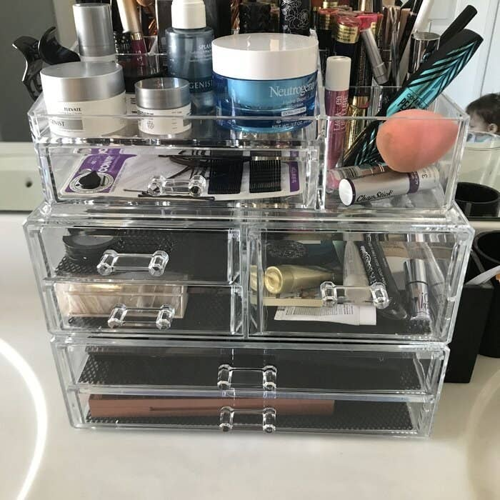 A clear plastic cosmetic organizer with multiple drawers and compartments filled with various makeup products