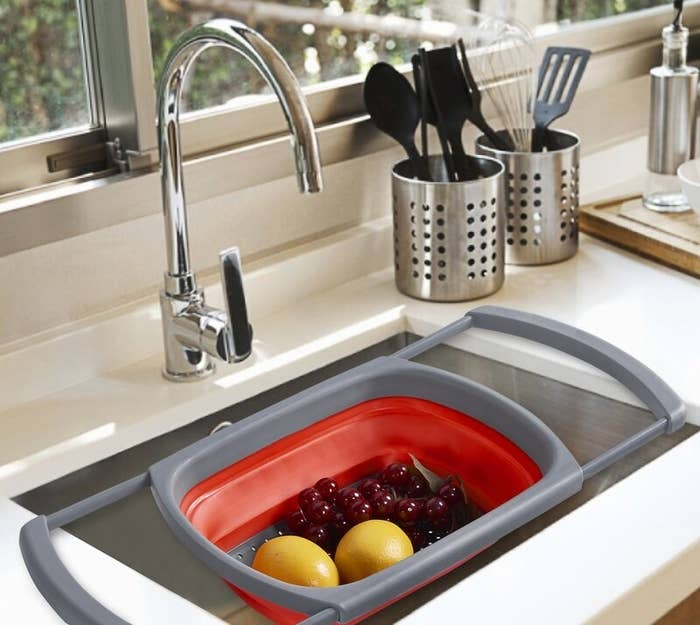A red plastic colander with gray arms extended and suspending itself with freshly washed fruit inside a sink
