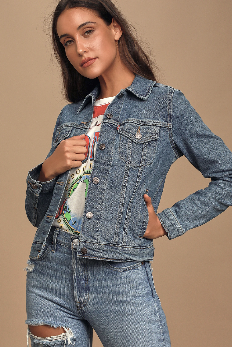 A model wearing a medium wash denim jacket over a shirt and jeans