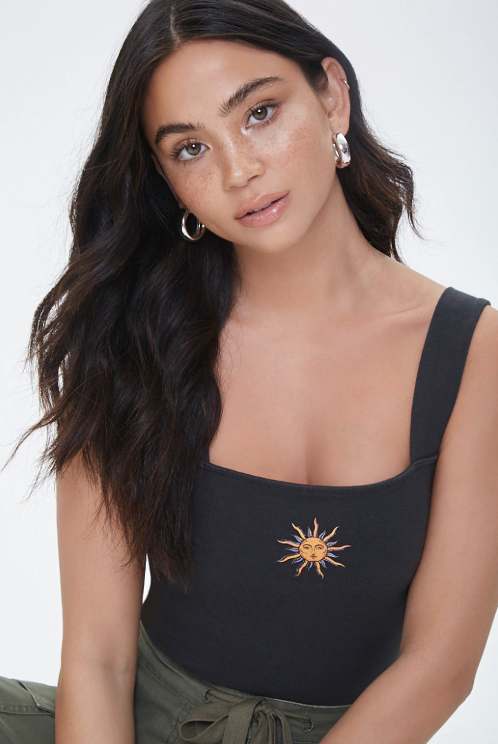 a person wearing a black crop top with thick straps and a non-cartoon like sun radiating from the middle of it