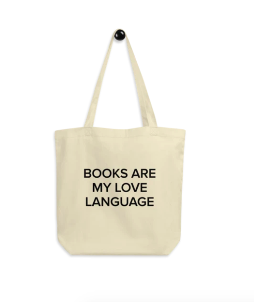 "A tote-bag that reads ""Books Are My Love Language"" in black text in the center"