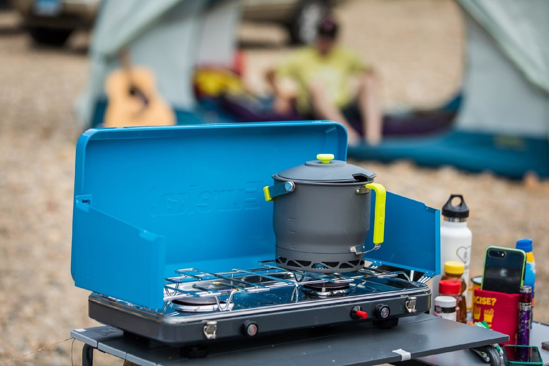 The blue burner camp stove with a pot on top of it