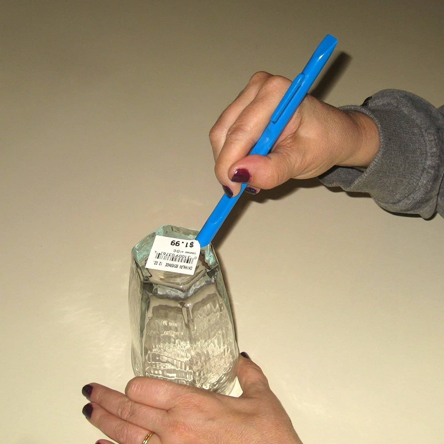 person with painted nails holding pen-like plastic tool in one hand, a glass in another hand, using the tool to scrape off a sticker on the bottom of the glass