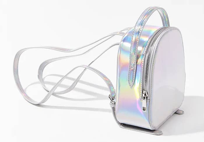 an iridescent mini backpack with long adjustable straps that looks almost rainbow colored in the light