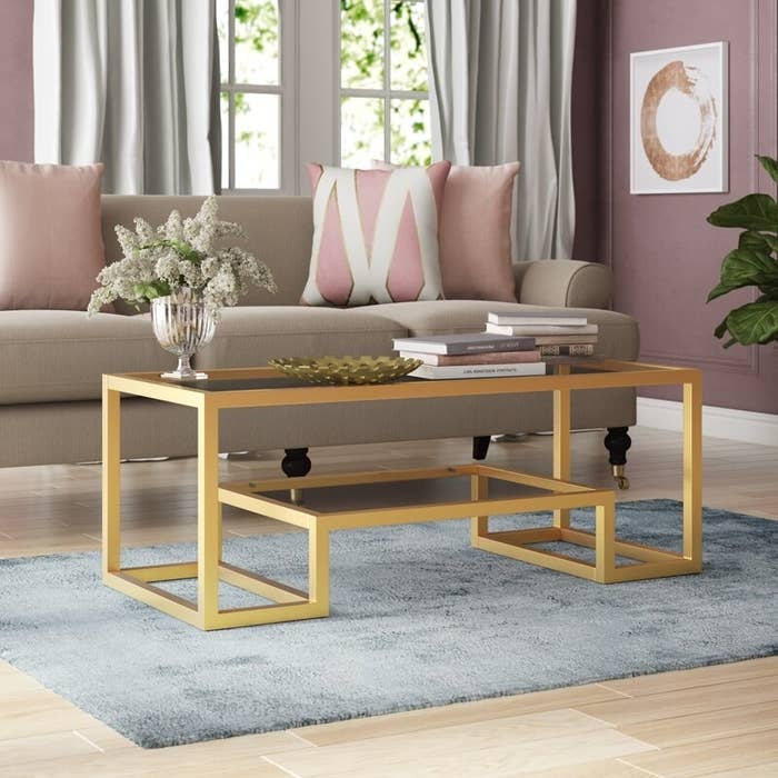The table with gold metal trim, a glass top, and a shelf underneath it that also has a glass top and gold trim