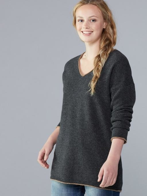 A grey V-neck sweater paired with blue jeans
