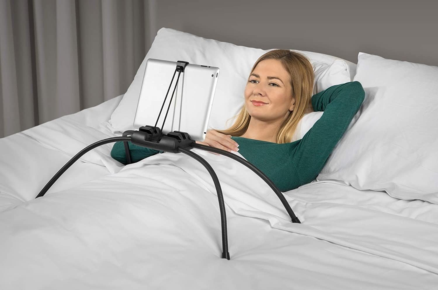 woman under the covers in bed with a tablet stand that has four bendable legs propped up on the bed so she can look at the screen without holding it