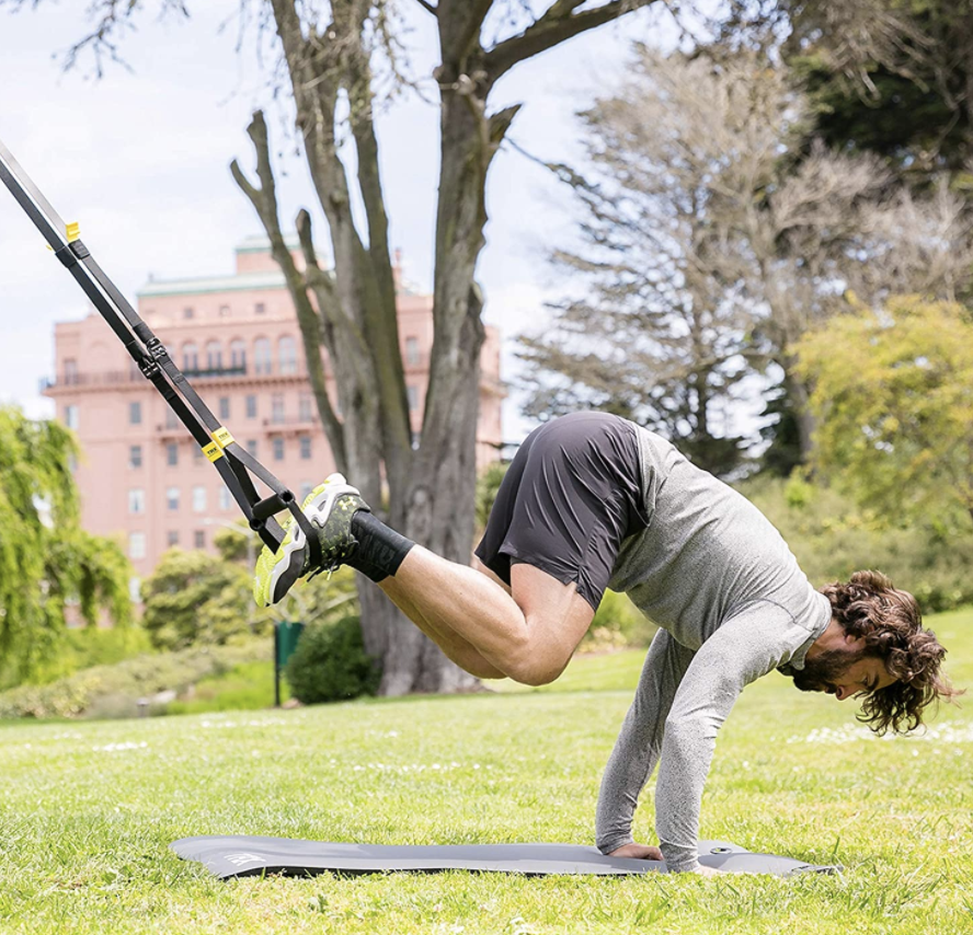 A model completes a pike movement with the TRX GO Suspension Training system above a mat outside