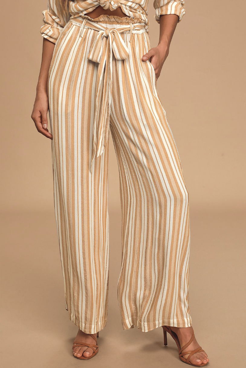 A waist-down image of a model wearing yellow and white striped pants with a tie-front waist and wide-leg style