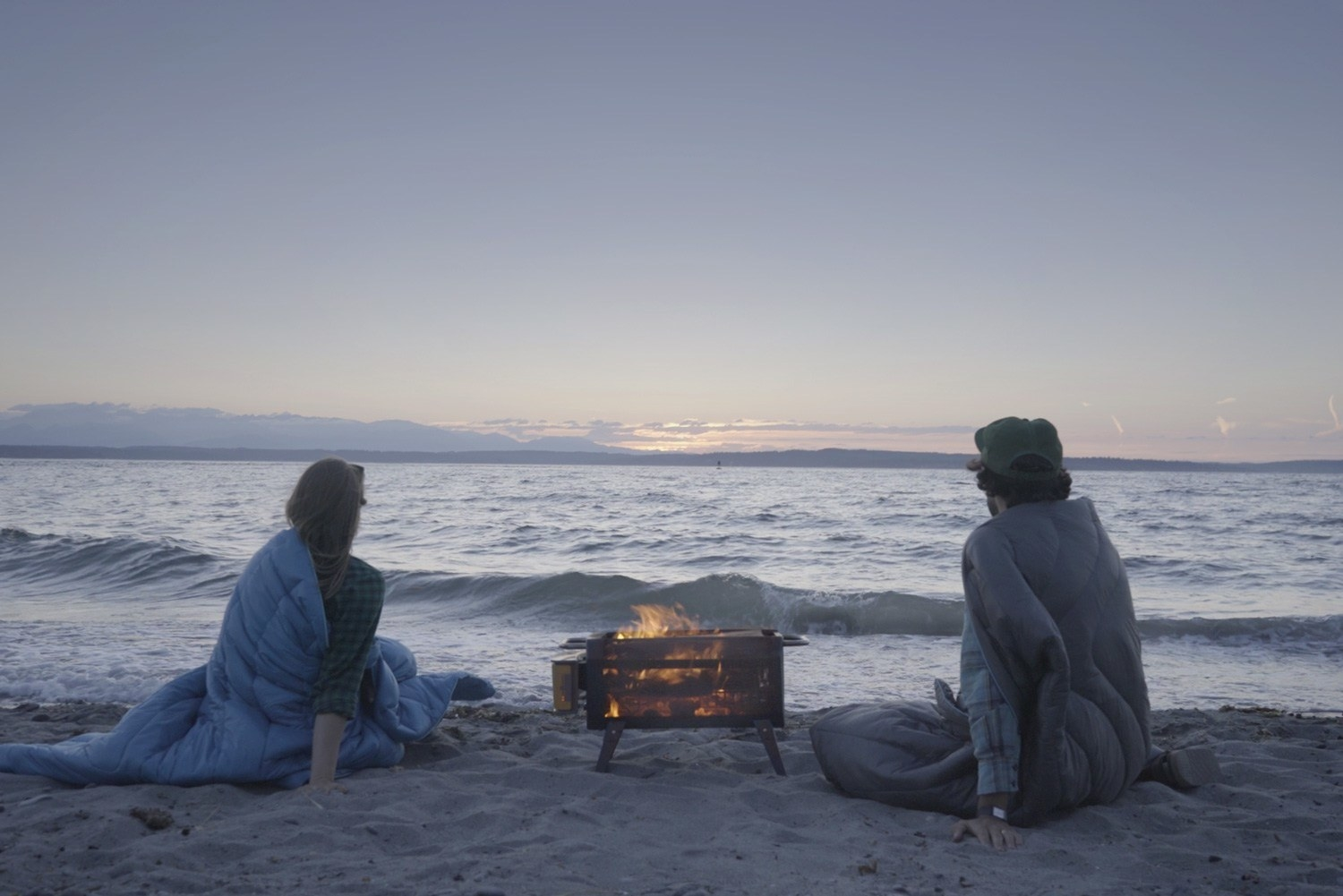 Two people enjoying the fire pit by the beach