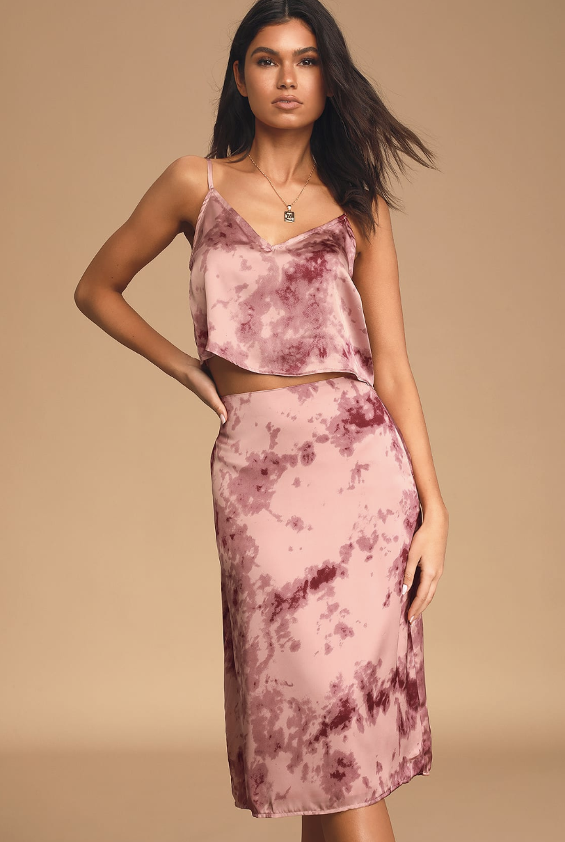 A model wearing a pink tie-dye midi skirt that falls just below her knee and a cropped cami to match