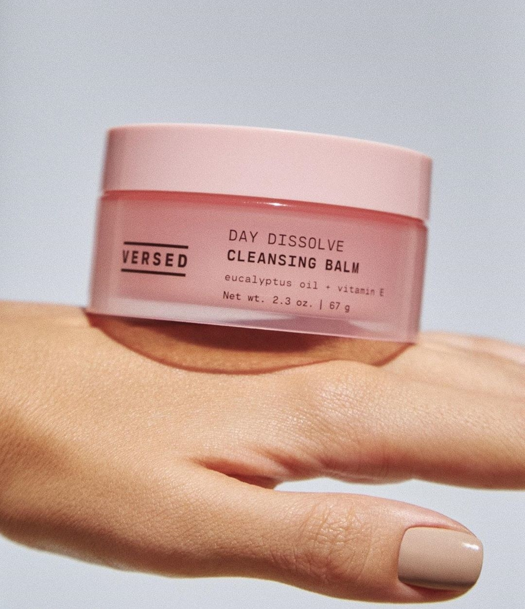 Model's hand holding a jar of the cleansing balm