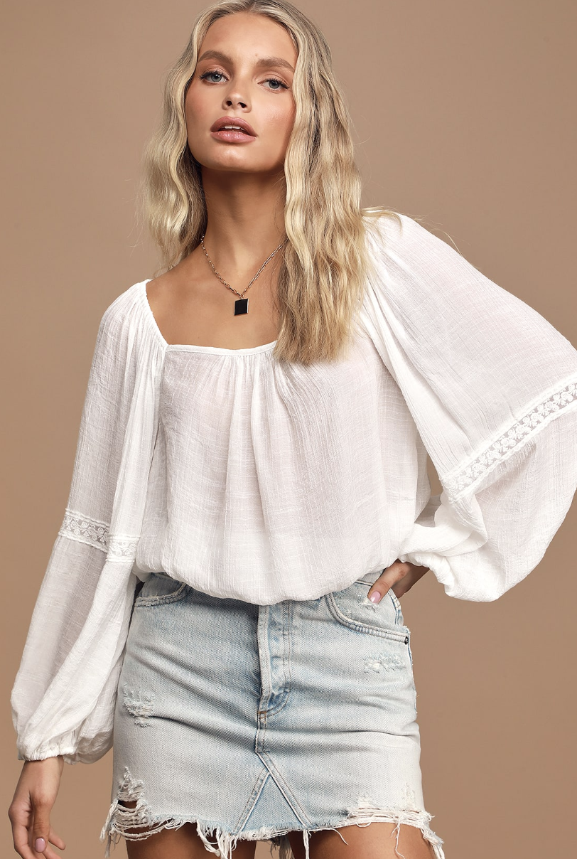 A model wearing a white balloon sleeve top with crochet details at the elbows. The top appears to be very lightweight in material