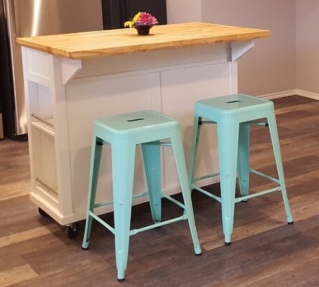 Two glossy teal blue metal counter stools on a wood floor underneath a white island table