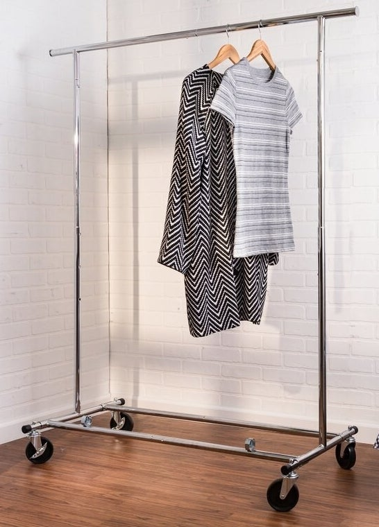 A metallic garment wrack on four caster wheels holding to items of clothing against a white wall and hardwood floor