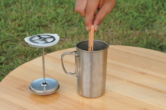 Hand using titanium coffee pot next to plunger