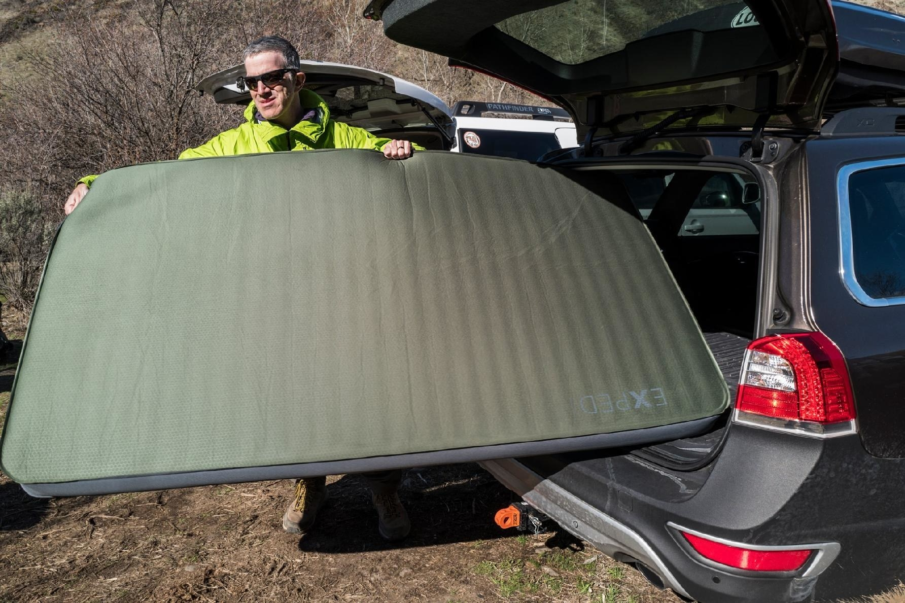 A person taking the sleeping pad out of the trunk of their car