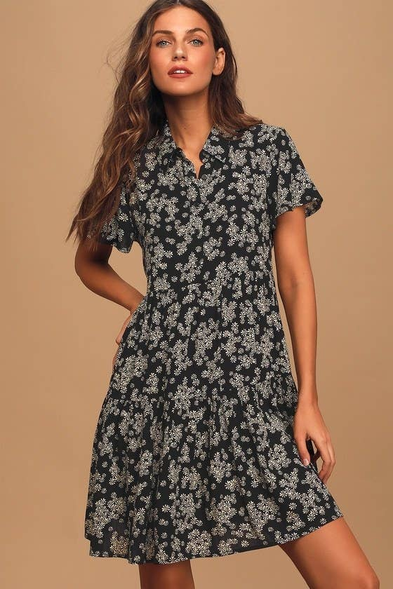 Model wearing black tiered short-sleeved shirtdress with small white floral design